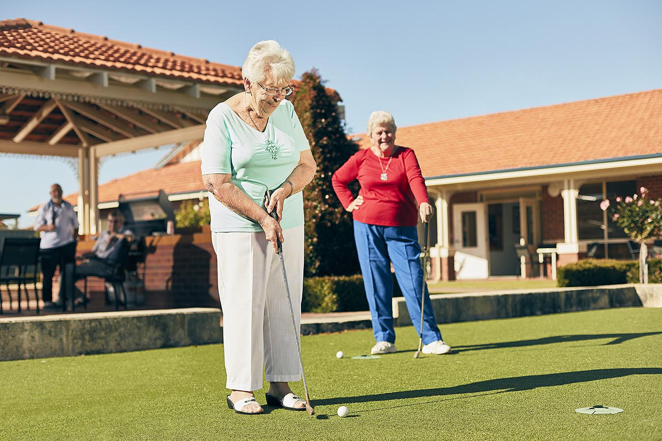 Retired woman enjoying putting a golf ball